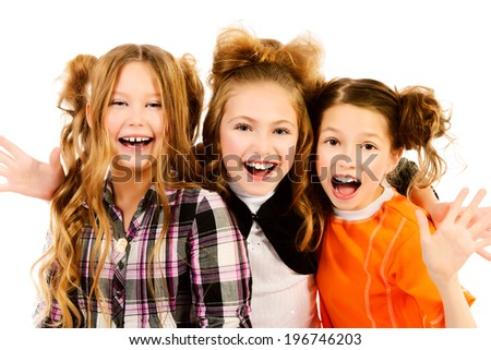Three happy girls standing together and laughing. Isolated over white. - stock photo
