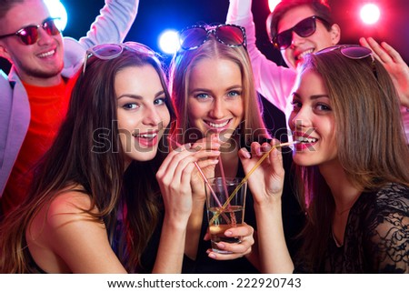 Three happy girls together drinking cocktails at a party - stock photo