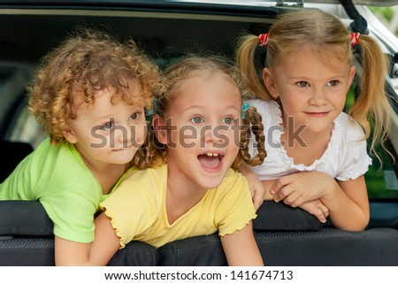three happy kids in the car - stock photo