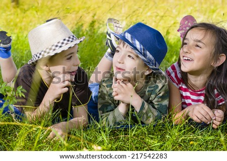 Three happy kids on grass in summer day - stock photo