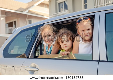 three happy kids sitting in the car - stock photo