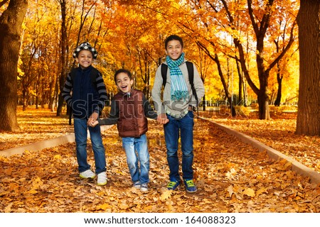 Three happy, laughing  boys, happy brothers 5-10 years old going together holding hands in the park wearing backpacks and autumn clothes in maple and oak park with lots of autumn orange leaves - stock photo