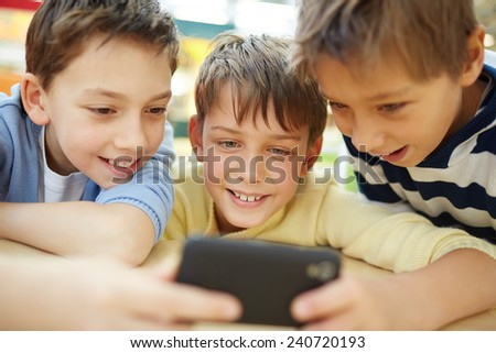 Three happy little boys using cellphone - stock photo