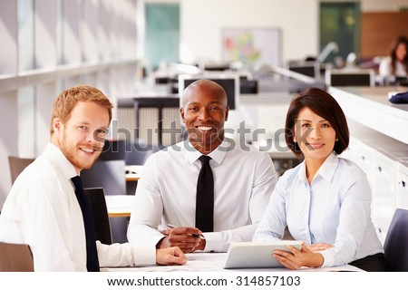 Three happy office colleagues looking to camera - stock photo