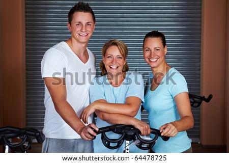 Three happy people standing around bikes in gym - stock photo