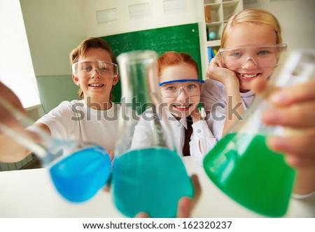 Three happy schoolchildren holding tubes with chemical liquids - stock photo