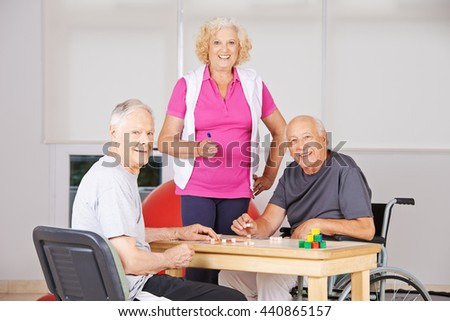Three happy senior citizens playing Bingo together in a nursing home - stock photo