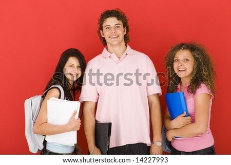 Three happy shoolmates holding notebooks and looking at camera. Front view. - stock photo