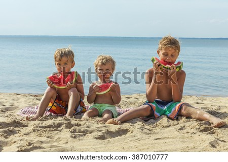 Three happy smiling child eating watermelon on the beach.  - stock photo