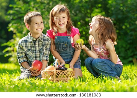 Three happy smiling child playing in park with fruits - stock photo