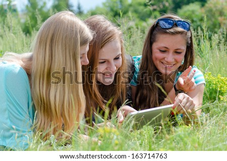 Three happy teen girl friends and tablet computer on summer outdoors background - stock photo