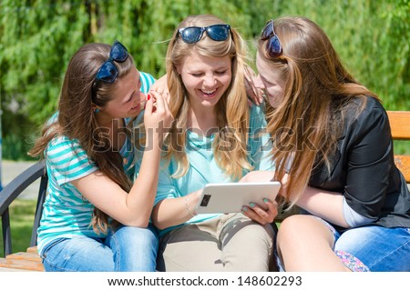 Three happy teen girl friends looking on tablet pc while sitting on bench outdoors on the summer day green background - stock photo