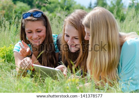 Three happy teen girl friends looking on tablet pc while sitting on green lawn on the bright sunny day & green summer outdoors - stock photo