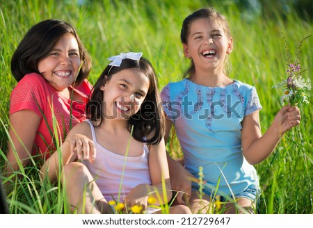 Three happy teen girls having fun at park - stock photo
