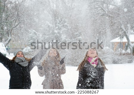 Three happy teenage girls throwing snow in the air. - stock photo