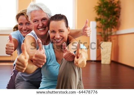 Three happy women in a gym holding their thumbs up - stock photo