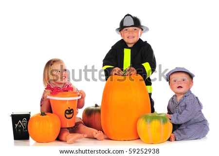 Three happy young children dressed for a happy Halloween, surrounded with pumpkins and trick-or-treat containers.  Isolated on white. - stock photo
