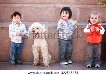 Three happy young children with  pet  dog. Outside - stock photo