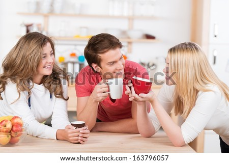 Three happy young college students having coffee together in the kitchen laugh and smile as they group around the wooden counter - stock photo