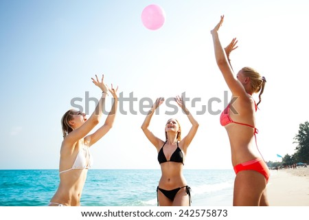 Three happy young girlfriends playing volleyball at the tropical beach, unfocused - stock photo
