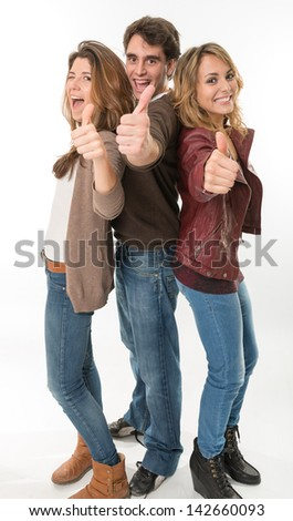 Three happy young people with thumbs up - stock photo