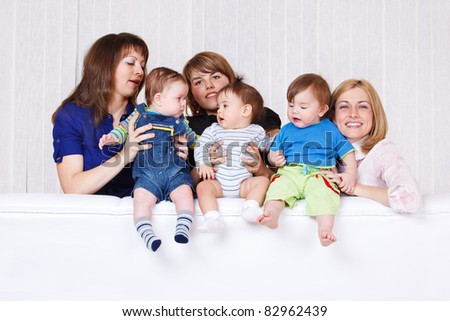 Three happy young women holding their babies - stock photo