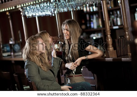 Three happy young women in a nightclub sitting at the bar - stock photo