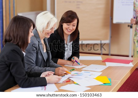 Three hardworking female business colleagues having a meeting sitting at a table together discussing paperwork and graphs - stock photo