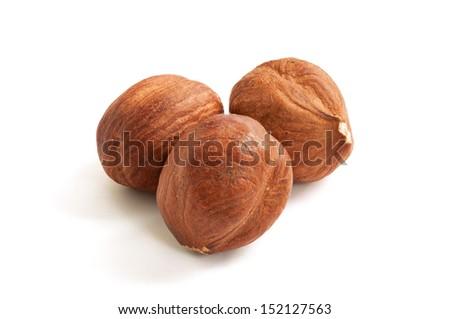 Three hazelnuts isolated on white background, macro image - stock photo