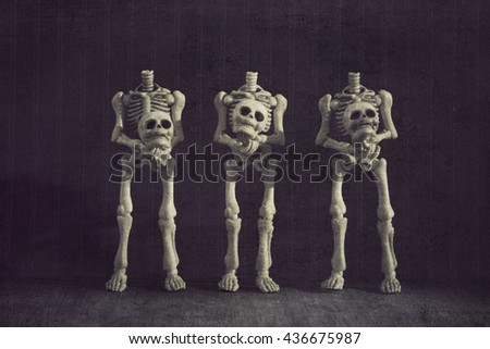 Three headless skeletons grungy textured - stock photo