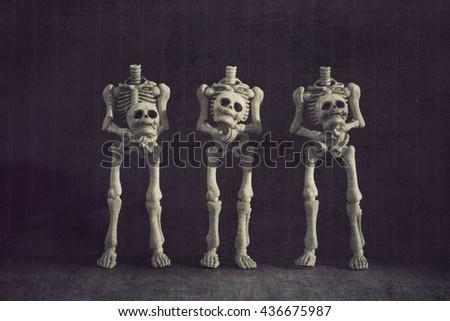 Three headless skeletons grungy textured - stock photo