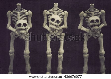 Three headless skeletons holding their heads with black background grungy textured - stock photo