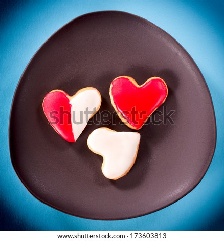 Three heart shape cookies in the plate on blue background - stock photo