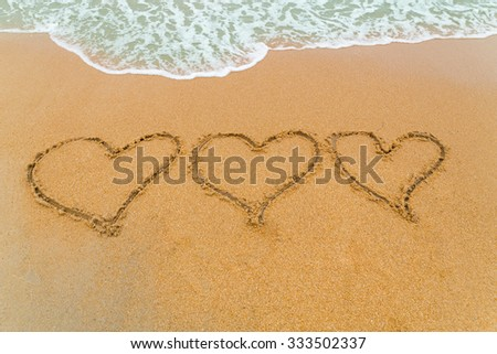 Three hearts drawn on serene sandy beach with soft blue wave approaching signifying I love You - stock photo