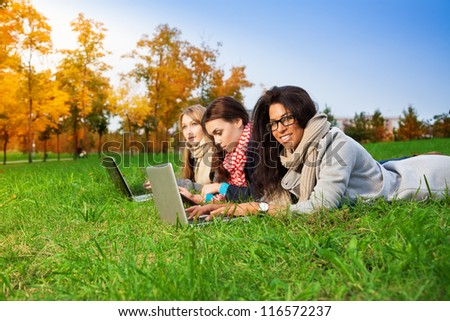 three high school students laying with laptops in the park - stock photo