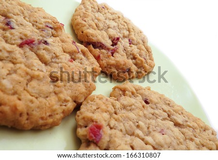 Three homemade cranberry oatmeal cookies on green plate  - stock photo