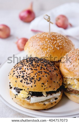 Three Homemade veggie burgers with sweet potato, black rice and red beans, served on white plate with kitchen towel over white textured background. - stock photo