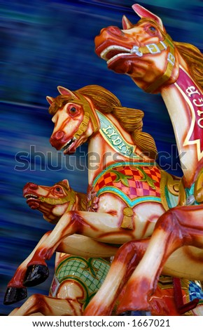 Three horses of a merry-go-round. Focus is on the middle horse. - stock photo