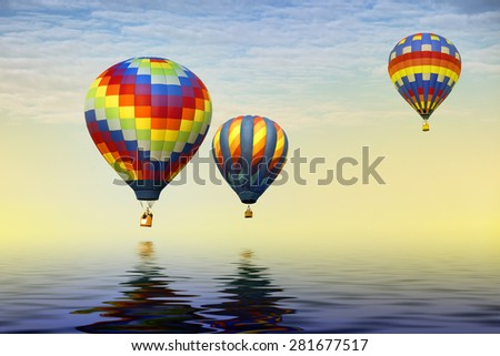 Three hot air balloons adrift over the ocean and reflecting in the water. - stock photo