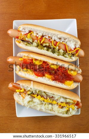 Three hot dogs on square plate , with mustard , ketchup , onion and relish , with chili , salsa and small tomatoes, and with sauerkraut , top view - stock photo