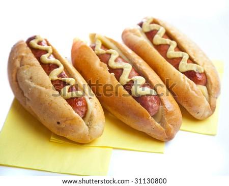 Three hot dogs on yellow napkin - stock photo