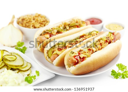 Three hot dogs with ingredients on a plate - stock photo