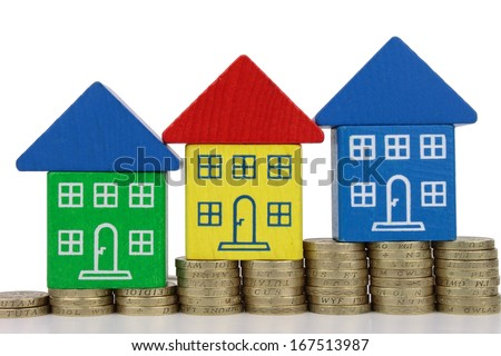 Three houses on rising column's of gold colored coins. - stock photo