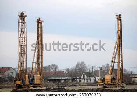 three hydraulic drilling machines on construction site - stock photo