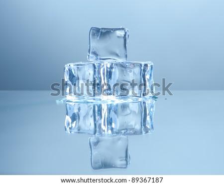 Three ice cubes on mirror - stock photo