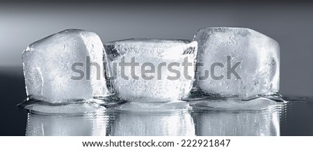 Three ice cubes with reflection on grey gradient background.  - stock photo