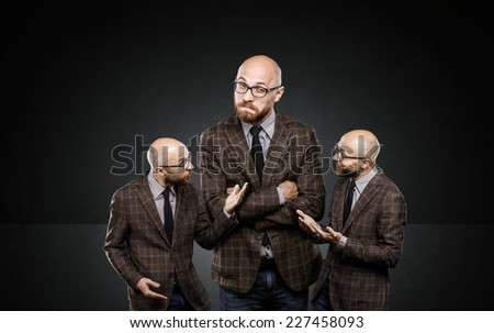 three identical men argue among themselves about important issues - stock photo