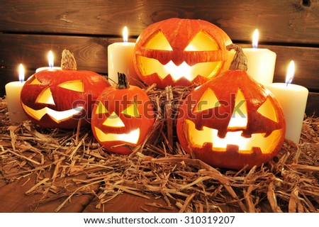 three illuminated halloween pumpkins and straw on old weathered wooden board in front of redbrown background in red light - stock photo