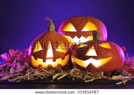 three illuminated halloween pumpkins in crazy violet halloween light and straw on old weathered wooden board in front of violet background - stock photo