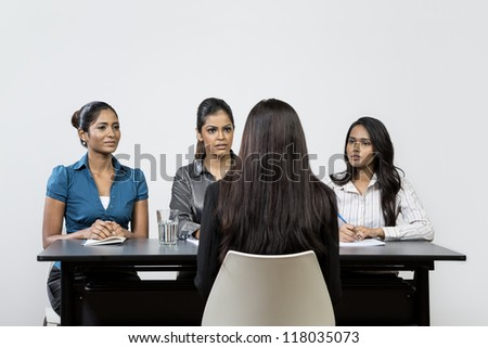 Three Indian colleagues from HR department interview a young female applicant. - stock photo